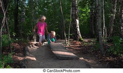 Sister and brother walk through barefoot path. Active children walking board