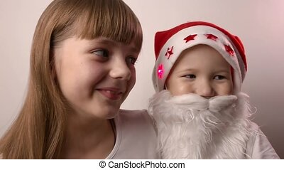 sister and brother with artificial beard in Santa Claus hat smile, laugh together