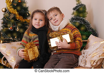 Sister and brother with golden presents under Christmas tree