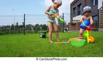 Sister and little brother play with water toys in backyard. Children have fun