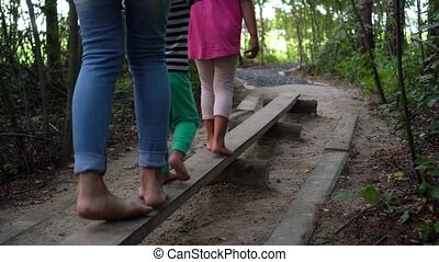 Sister brother and mother walk through narrow board. Active children with mom