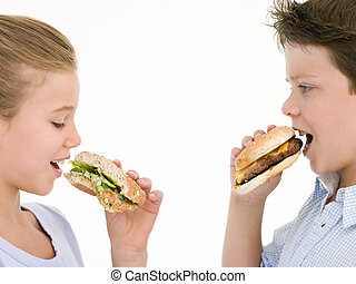 Sister eating sandwich by brother eating cheeseburger