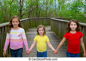 sister friends walking holding hands on lake wood