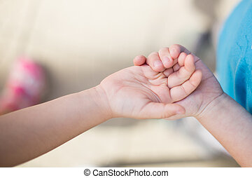 sister holding baby hand