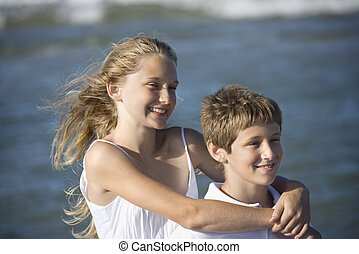 Sister hugging brother on beach.
