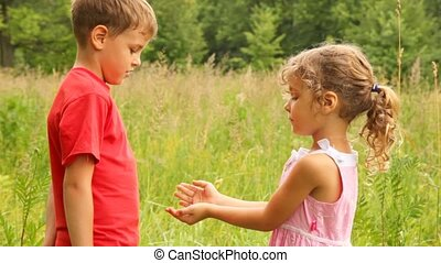 Sister is blowing on brother in the park
