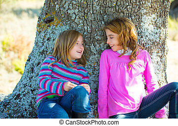 Sister kid girls smiling sit relaxed in a oak tree trunk...