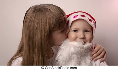 sister kisses brother with artificial beard in Santa Claus hat, smiles, laughs