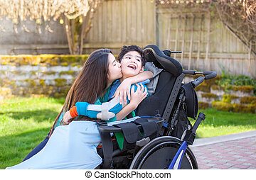 Sister kissing and hugging disabled little brother in wheelchair outdoors