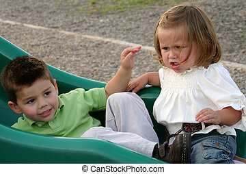 Angry young girl sitting on a sliding board with her brother, who is ignoring her.