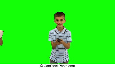 Sister pouring popcorn on brothers head on green screen in...