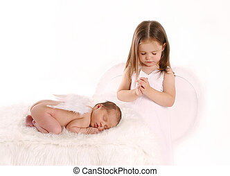 Portrait of beautiful newborn wearing angel wings with older sister standing by saying prayers