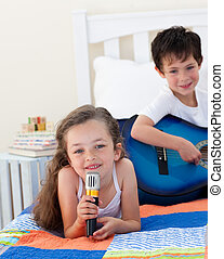 Sister singing and brother playing guitar