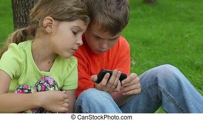 Sister watches how her brother plays with digital game on cell phone, when kids sit together at grass near tree, closeup view