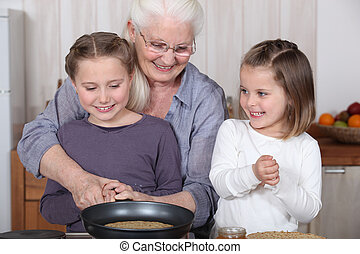 Sisters cooking pancakes with grandmother