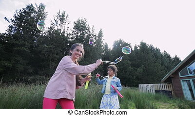 Sisters Creating Some Bubbles Outside - Slow motion, low...