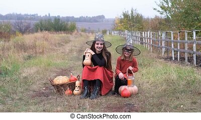 Smiling sisters dressed for halloween sitting on nature with pumpkins and candle