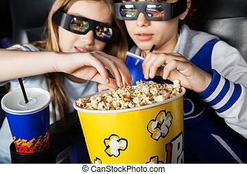 Sisters Having Popcorn In 3D Theater