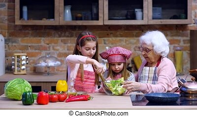 Sisters help granny to prepare salad - Two cute little...