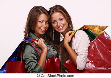 Sisters holding shopping bags on white isolated