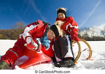 Sisters in snow on toboggan