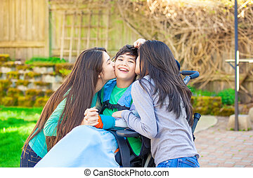 Sisters laughing and hugging disabled little brother in wheelchair outdoors