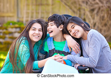 Sisters laughing and hugging disabled little brother in...