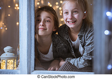 Sisters looking through the window