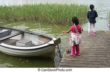 Sisters palying in the nature with a boat