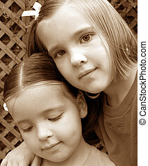 Sisters - Big sister with arm around little sister - heads...