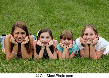 Sisters Laying in Grass in a Row