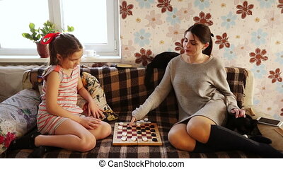 Sisters playing checkers - Sisters play checkers at home on...