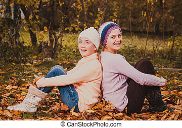 Sisters playing with leaves