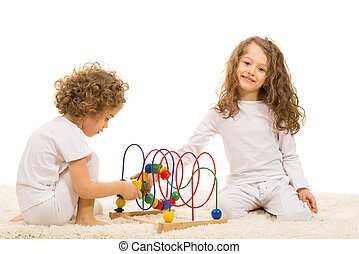 Sisters playing with wooden toy home