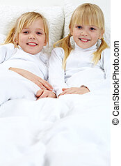 Sisters - Portrait of two adorable sisters lying in the bed