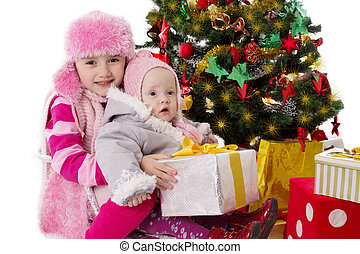 Sisters sitting with gifts under Christmas tree