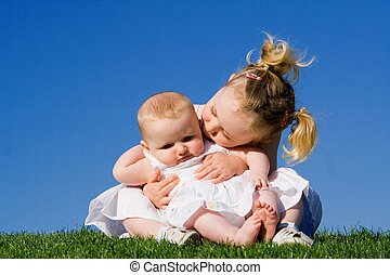 sisters, toddler and baby girls outdoors in summer
