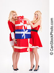 Sisters twins in santa claus costumes carrying heavy present boxes