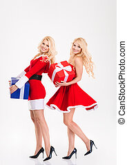 Sisters twins in santa claus costumes dancing with present boxes