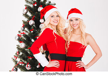 Sisters twins in santa claus costumes standing near Christmas tree
