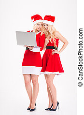 Sisters twins in santa claus dresses and hats with laptop