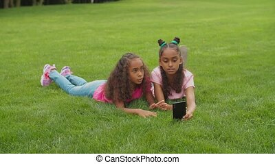 Positive adorable preadolescent african sisters lying on green grass, video conferencing online using smart phone, chatting and live streaming while enjoying leisure together in summer nature,