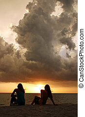 Two young sisters watching amazing tropical sunset from Sanibel Island, Florida