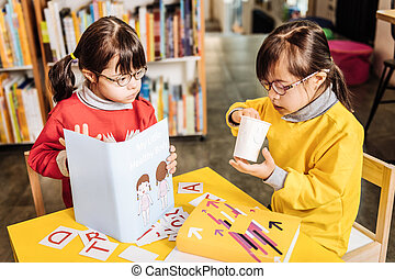 Sisters with genetic disorder wearing bright sweaters learning letters