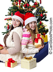 Sisters with gifts under Christmas tree