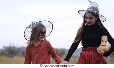 Smiling sisters with halloween makeup and costumes walking holding hands in autumn nature