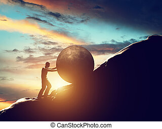 Sisyphus metaphor. Man rolling huge concrete ball up hill. Sisyphean work, task.