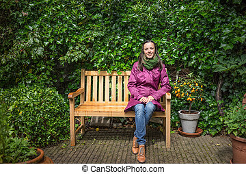 Sit on the bench after rain - Beautiful young woman sits on...