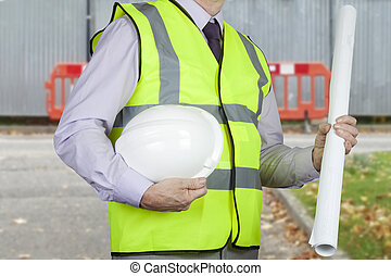 Site engineer in hi-viz holding drawings and hard hat