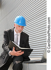 Site manager checking planning on computer